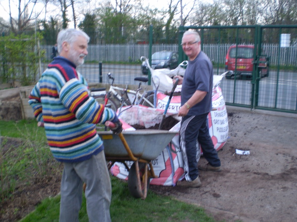 Picture of Colin and the other Barry filling the barrow with top soil
